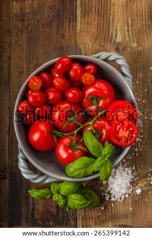 Fresh tomatoes in a bowl with basil and salt - stock photo