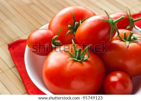 fresh tomatoes in white bowl on red napkin