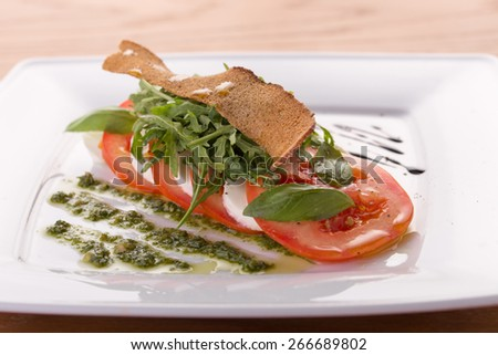 Fresh tomatoes, mozzarella cheese and toasts on plate on wooden background