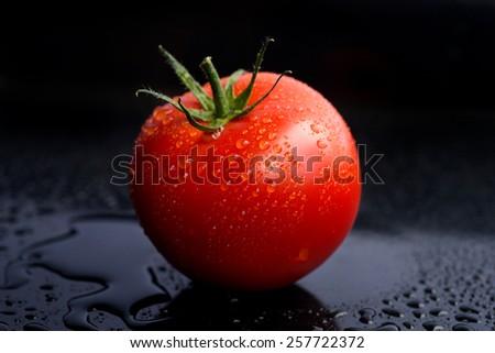 fresh tomatoes on a black background - stock photo