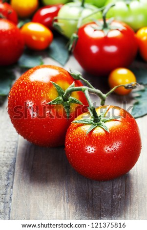 Fresh tomatoes on a wooden table top - stock photo