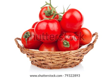 fresh tomatoes on green branch in wicker basket isolated on white background - stock photo