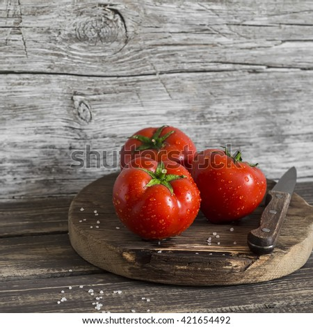 Fresh tomatoes on rustic wooden background - stock photo