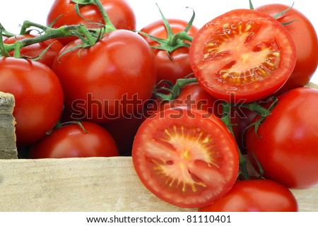 fresh tomatoes on the vine and a cut one in a wooden crate on a white background - stock photo