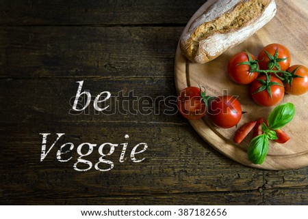 fresh tomatoes with basil and rustic bread on wooden table, text be veggie - stock photo
