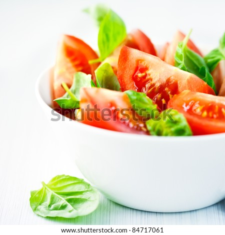 Fresh tomatoes with basil leaves in a bowl - stock photo