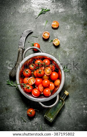 Fresh tomatoes with olive oil and a knife. Wet stone background.  - stock photo