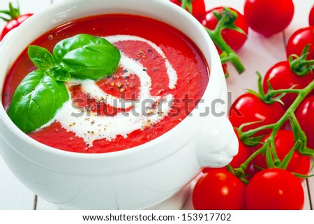 Fresh tomatoes with tasty tomato soup drizzled with cream and sprinkled with ground pepper topped with fresh basil - stock photo