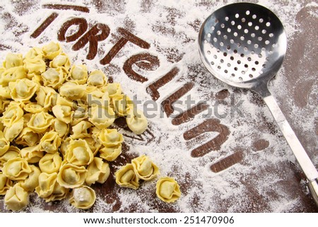 Fresh tortellini and utensil with flour on wooden table - stock photo