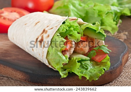 Fresh tortilla wraps with chicken nuggets and vegetables on plate - stock photo
