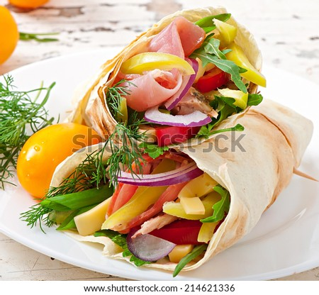 Fresh tortilla wraps with meat and vegetables on plate - stock photo