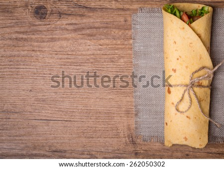 fresh tortilla wraps with vegetables on wooden background top view - stock photo