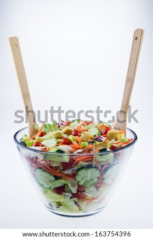 Fresh tossed garden salad in a glass bowl with wooden spoons set against a white background. - stock photo