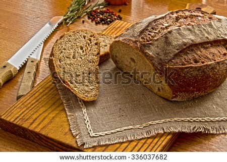 Fresh Tradition sliced bread loaf on the kitchen table with Spices and kitchen utensils - stock photo
