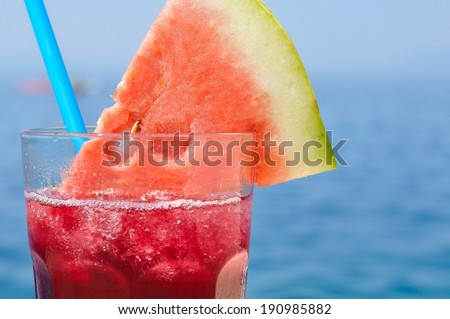 Fresh tropical fruit cocktail with water melon slice on a beach.  Blurred sea on background. Space on right side - stock photo