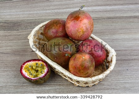 Fresh tropical fruit - Passionfruit - in the basket o wood background - stock photo