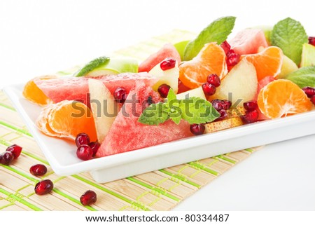 Fresh tropical fruit salad in white plate. Summer background. - stock photo