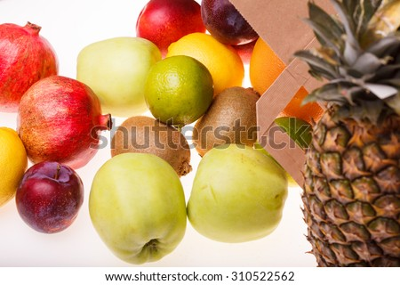 Fresh tropical fruits of pineapple orange juicy grapefruit yellow lemon ripe nectarine purple plum red pomegranate kiwi lime and green apple and paper pack on white background, horizontal picture - stock photo