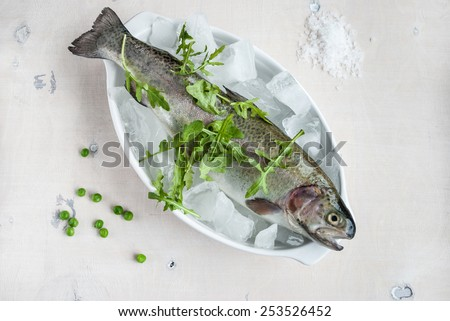 Fresh trout on ice with arugula, sea salt and green peas