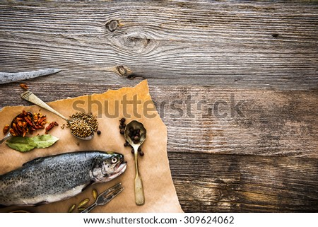 fresh trout with seasonings in a spoons on a table - stock photo