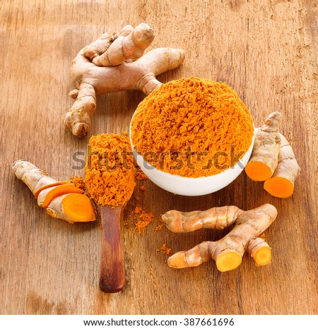 fresh turmeric roots with turmeric powder on wooden table - stock photo