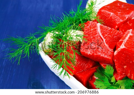 fresh uncooked beef meat slices over white bowls ready to prepare with green hot peppers and greenery serving over blue wooden table - stock photo