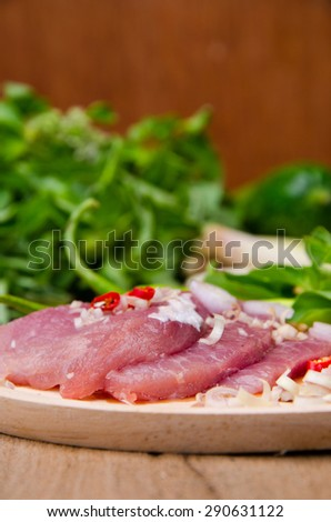 fresh uncooked beef meat slices over wooden cutting board ready to prepare with green hot and red peppers isolated - stock photo