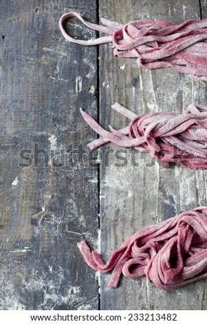 fresh uncooked homemade pasta tagliatelle with beetroot on rustic wooden table with flour - stock photo
