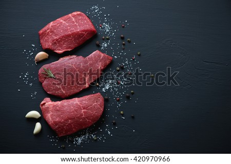 Fresh uncooked marbled beef schnitzels on a black wooden surface, above view