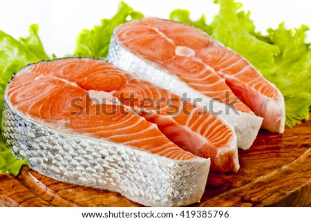 Fresh uncooked Pacific Coast Salmon with lettuce and a lemon wedge. - stock photo