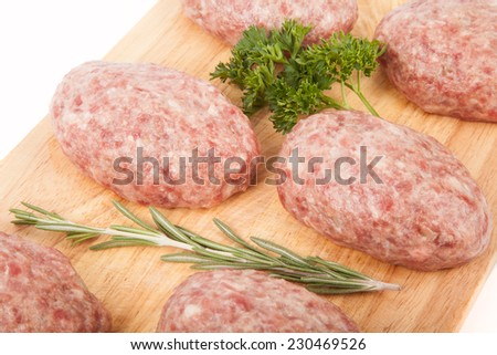 fresh uncooked patties on a wooden board with rosemary and parsley - stock photo