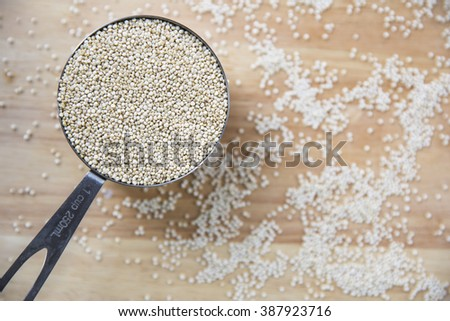 Fresh uncooked quinoa in measuring cup from above. - stock photo