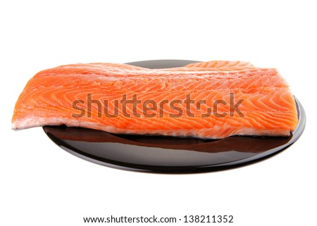 fresh uncooked red fish fillet on black over white - stock photo