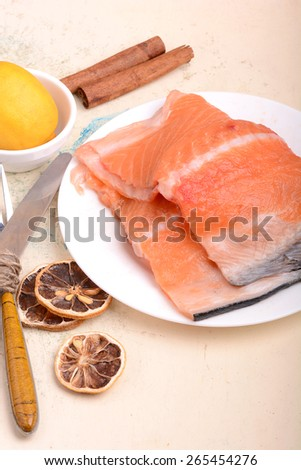 Fresh uncooked red fish fillet slices and cinnamon - stock photo