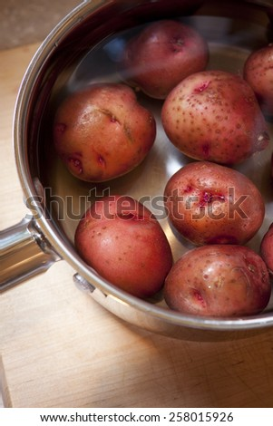 Fresh uncooked red new potatoes in a silver stainless steel pot.