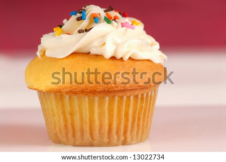 Fresh vanilla cupcake with lemon buttercream frosting and sprinkles - stock photo