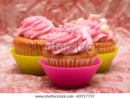 Fresh vanilla cupcakes in pink cups with strawberry icing and marshmallows on decorative background - stock photo