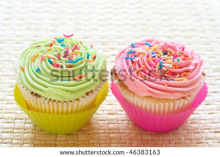 Fresh vanilla cupcakes with strawberry and lime icing on woven straw ...