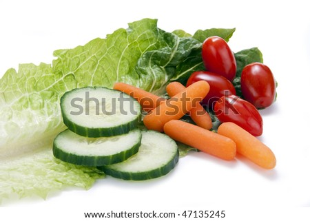 Fresh vegatables (cucumbers, carrots, and cherry tomatoes) on a single leaf of Roamaine lettuce. - stock photo