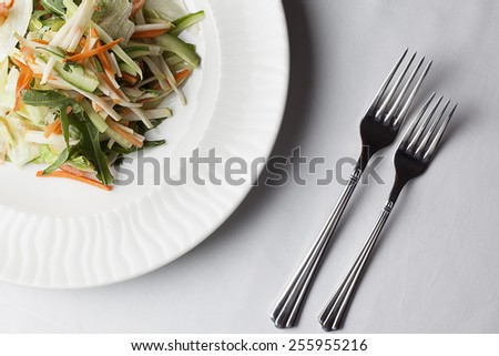 Fresh vegetable mix salad with arugula, carrots, cucumber and paprika with fork. - stock photo