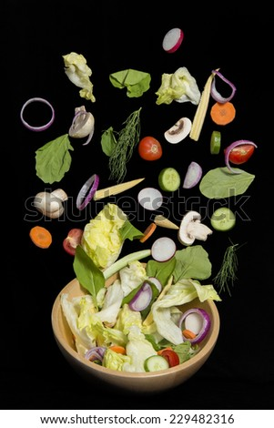 Fresh vegetable salad falling isolated on black background - stock photo