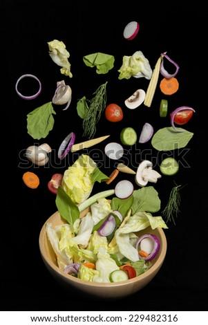 Fresh vegetable salad falling isolated on black background - stock photo