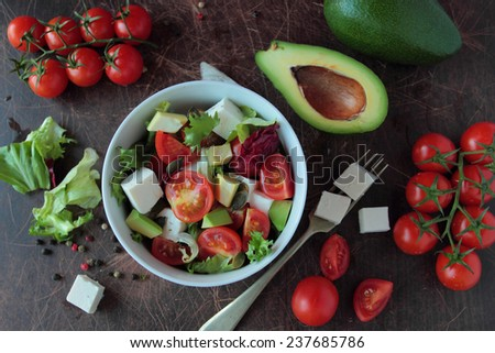 Fresh vegetable salad in a bowl on wooden board - stock photo
