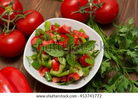 fresh vegetable salad in a white mask on a wooden table - stock photo