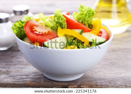 Fresh vegetable salad on grey wooden background - stock photo