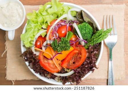 fresh vegetable salad on wood background - stock photo