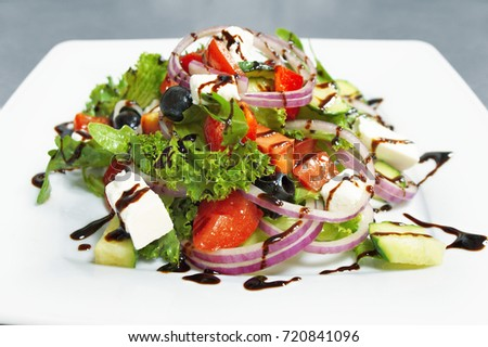 fresh vegetable salad  with balsamic cream, feta and olives.close-up