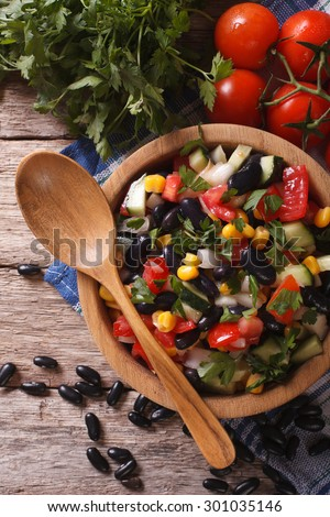 Fresh vegetable salad with black beans in a wooden bowl close-up and ingredients on the table. vertical top view - stock photo
