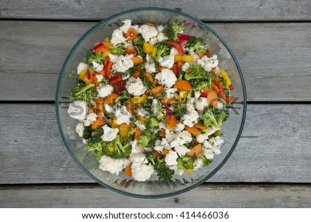 Fresh vegetable salad with cauliflower, broccoli, carrots and peppers in glass bowl, overhead view - stock photo