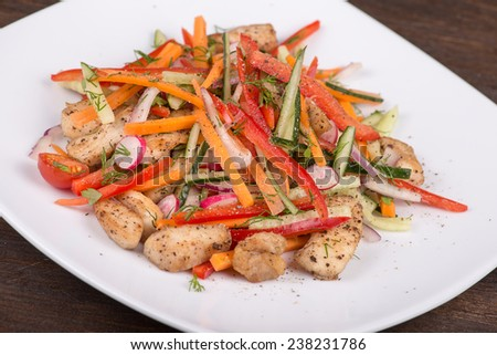 Fresh vegetable salad with chicken meat in white plate - stock photo